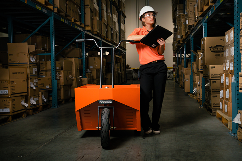 person standing in a warehouse next to an Optimus Industries scooter