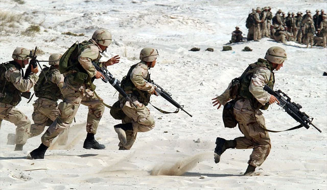 five soldiers running on sand